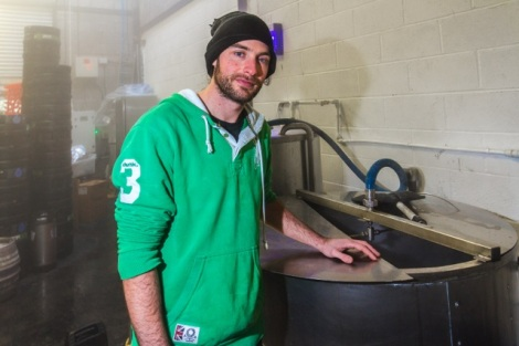 Cardiff, United Kingdom, November 26 2015. Brewer Adam stands by brewing equipment at the Crafty Devil Microbrewery, Canton, Cardiff, Wales.